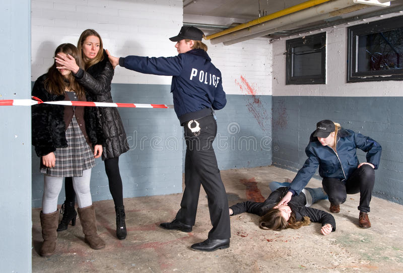 Keeping bystanders at a distance. Policeman setting the perimeter of a crime scene whilst keeping the bystanders at a distance. A mother is shielding off her royalty free stock photography