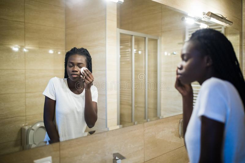 Beautiful young African woman clean face from cosmetics and smiling while standing against a mirror in bathroom royalty free stock image