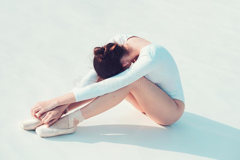 Keeping herself fit. Pretty woman in dance wear. Young ballerina sit on floor. Cute ballet dancer. Practicing the art of stock image