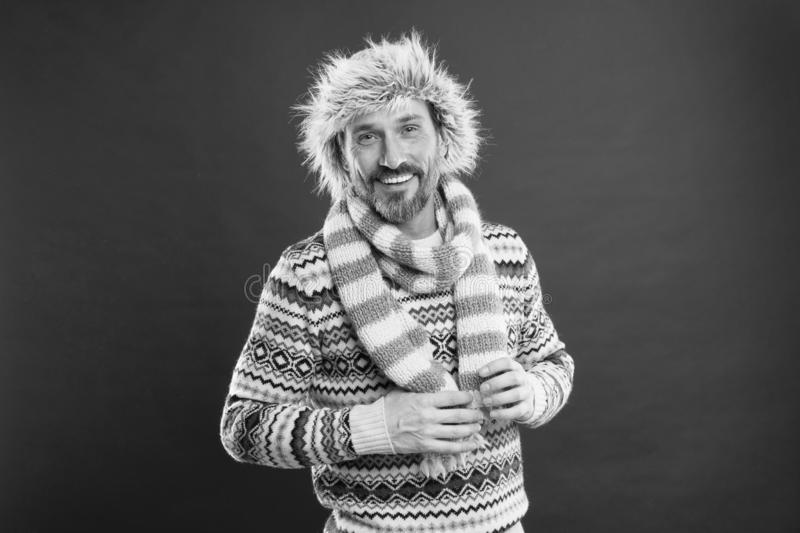 Keeping him warm. A winter ensemble protects him from cold. Bearded man accessorizing sweater with hat and scarf. Mature. Fashion model enjoys cold weather royalty free stock photo