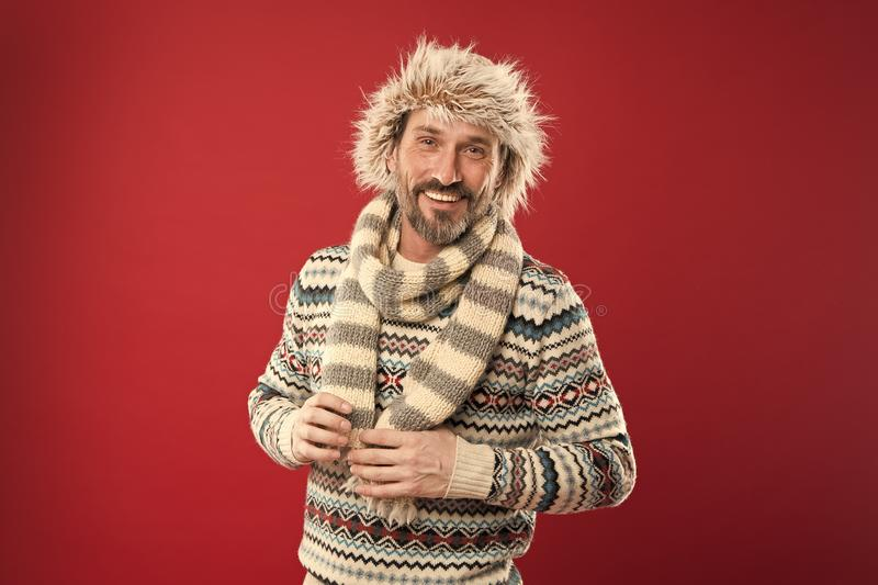 Keeping him warm. A winter ensemble protects him from cold. Bearded man accessorizing sweater with hat and scarf. Mature. Fashion model enjoys cold weather stock photos