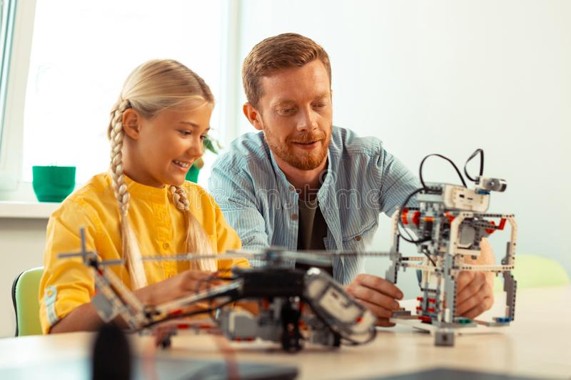 Smiling girl looking at her teacher building a robot. Keeping in mind. Smiling girl sitting with her teacher at the school desk looking at him building a robot royalty free stock photography