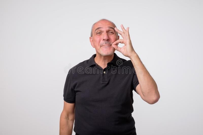 Keeping quiet and silence concept. Concept of mature amn zipping or closing his mouth stock photography