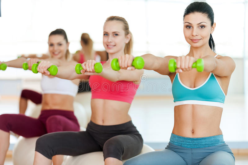 Keeping their bodies in shape. Three beautiful young women in sports clothing holding dumbbells and smiling at camera while sitting on the fitness ball royalty free stock photo