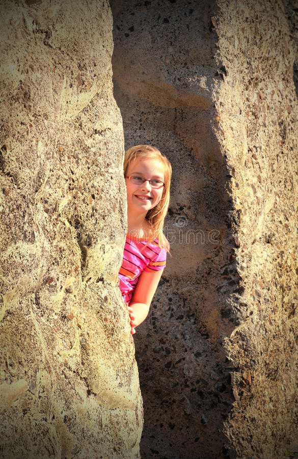 Keeping watch. A little blond haired smiling girl cautiously keeping watch from a hiding spot stock images