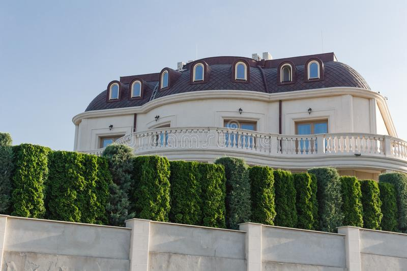 Keeps privacy and security concept. Big luxury house behind the green fence in Byala, Bulgaria. Keeps privacy and security concept. Big luxury house behind the royalty free stock photography