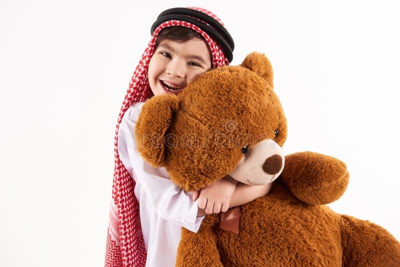 keffiyeh的阿拉伯愉快的男孩拥抱被充塞的玩具 免版税库存图片