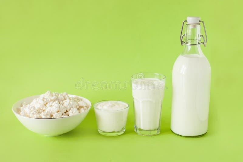 Kefir γάλακτος η ξινά κρέμα και το τυρί εξοχικών σπιτιών είναι σε μια σειρά σε ένα πράσινο υπόβαθρο Φρέσκα γαλακτοκομικά προϊόντα στοκ φωτογραφία με δικαίωμα ελεύθερης χρήσης