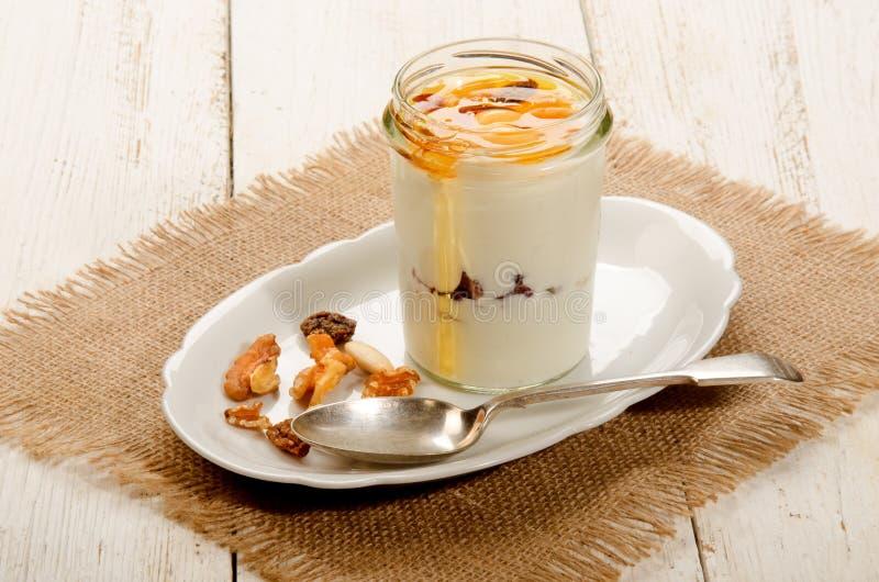 Kefir em um vidro com mel, as porcas e fruto doces fotografia de stock