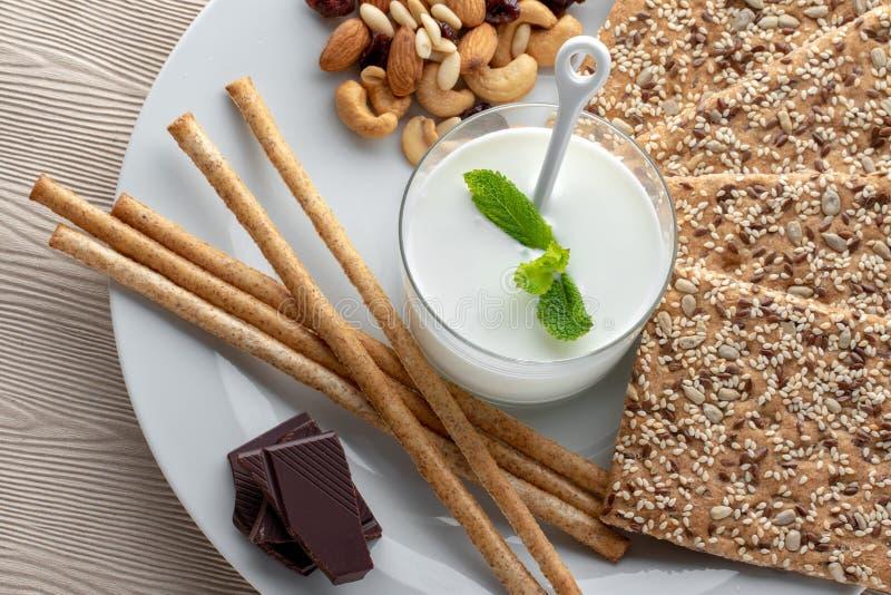 Kefir, porcas, varas de pão, biscoitos da semente de sésamo e chocolate escuro fotos de stock royalty free