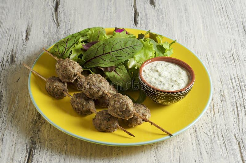 Keftedes, Griekse die kalfsvleesvleesballetjes met tzatzikisaus worden gediend stock afbeelding