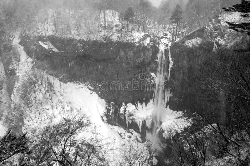 Kegon Fall is frozen during strong snowfall in winter season of Japan. Low contrast by black and white tone stock image