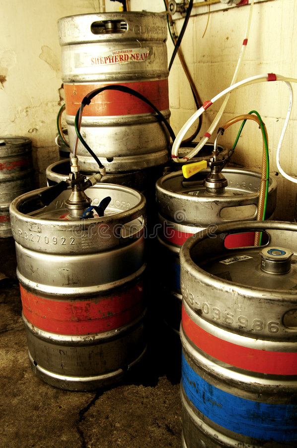Kegs in Basement of Pub. Several kegs are cooled in the basement of a British pub and hooked up to the taps on the main floor stock image