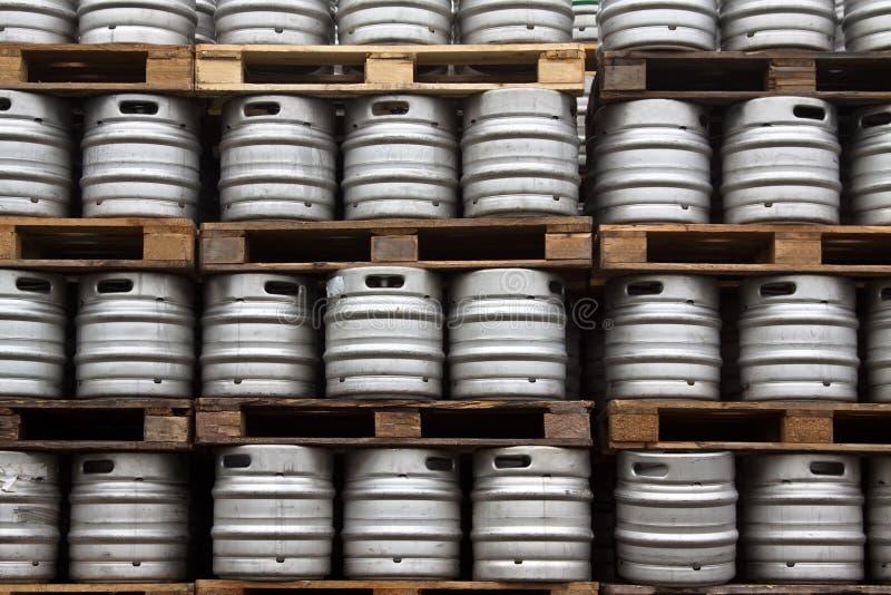 Kegs of beer in regular rows. Many metal kegs of beer in regular rows stock photo