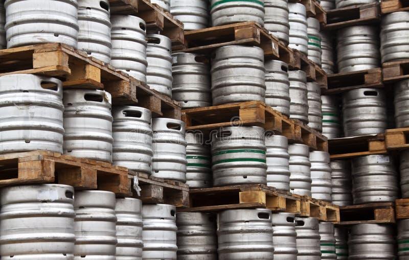 Kegs of beer in regular rows. Many metal kegs of beer in regular rows royalty free stock photos
