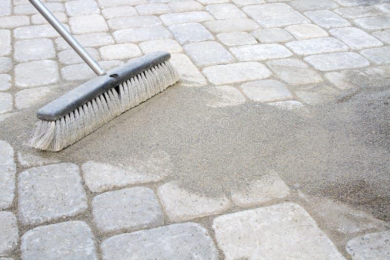 Kehren Sie ausgedehnten Sand in Straßenbetoniermaschinen stockbilder