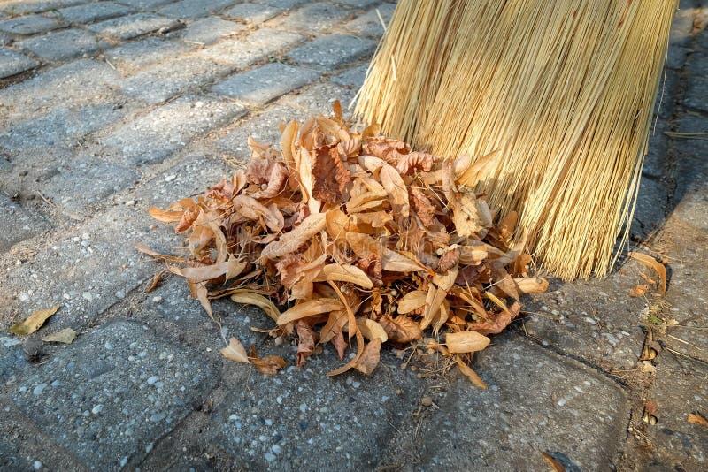 Kehren Sie fegende trockene Blätter in einem Haufen im Garten lizenzfreies stockbild
