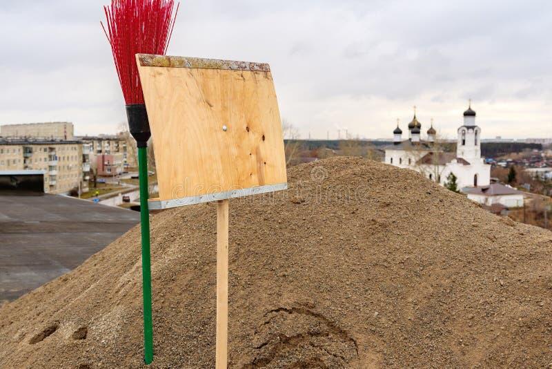 Kehren Sie roten Plastik und hölzerne Schaufel auf dem Hintergrund der Kirche, die im Sand gehaftet wird lizenzfreies stockfoto
