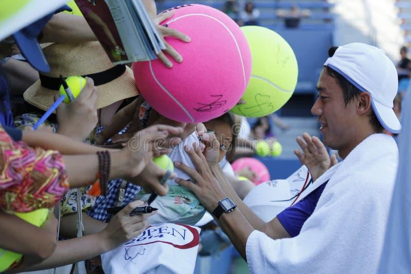 Kei Nishikori för yrkesmässig tennisspelare undertecknande autografer efter övning för US Open 2014 arkivfoto