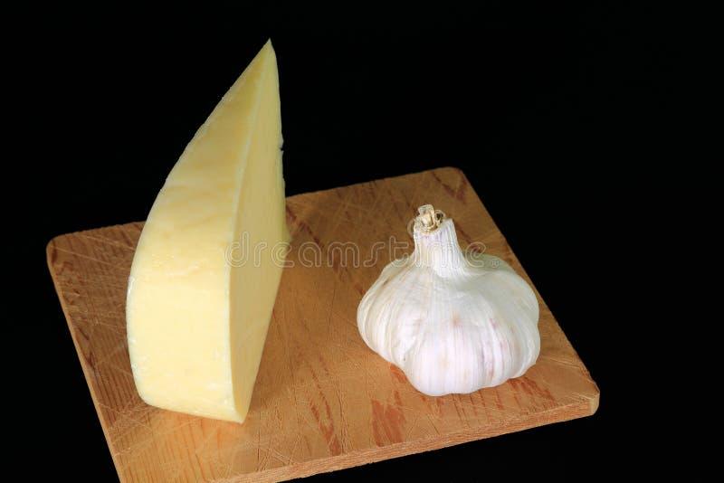 Keil Smocked-Gouda-Käse und organisch gewachsene Knoblauchknolle lizenzfreie stockfotos