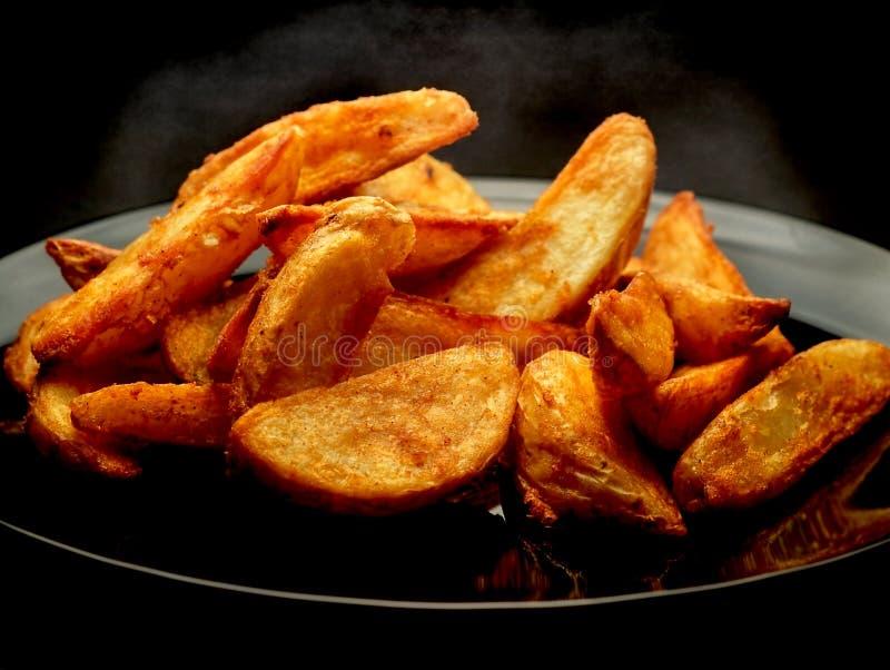 Keile der heißen Kartoffel auf schwarzer Platte stockbild