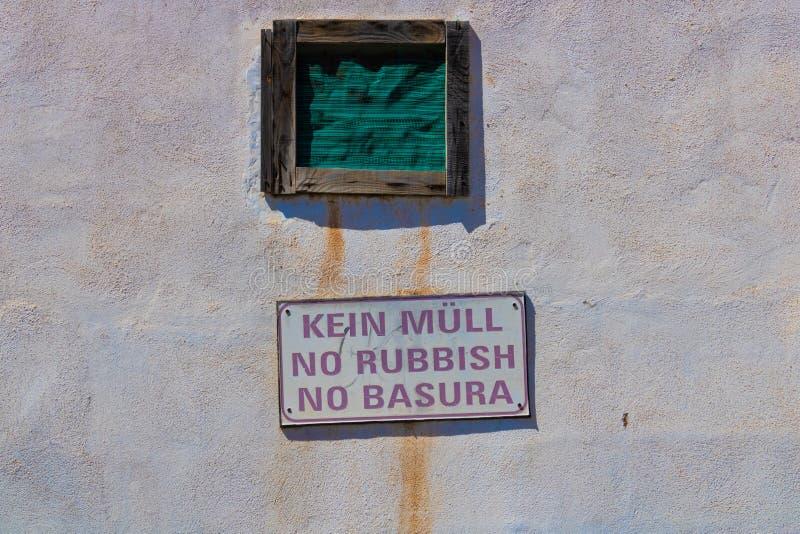 Kein Abfallzeichen auf Deutsch, Englisch und spanisch auf der schmutzigen Wand - Bild lizenzfreies stockbild