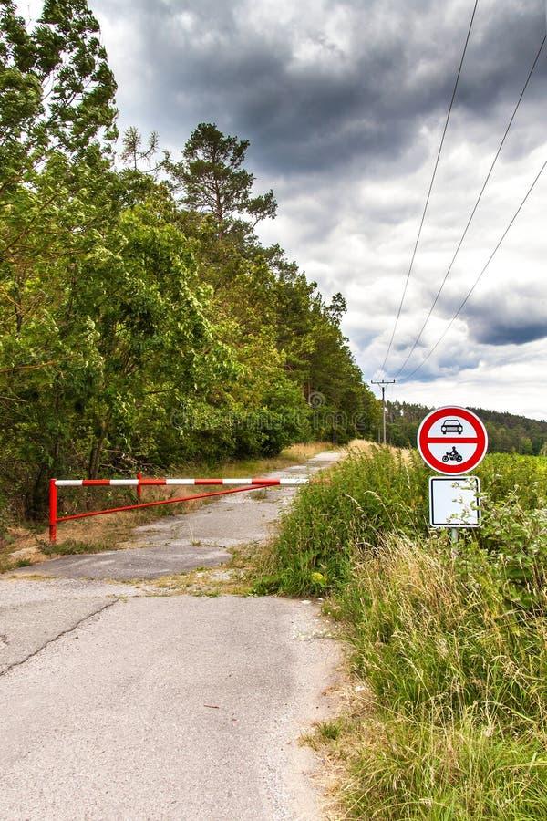 Kein Eintritt für Kraftfahrzeuge, fahrend nur gewährt rad Sturmwolken über Waldweg Geschlossener Eingang zum Waldwegzeichen lizenzfreie stockfotografie
