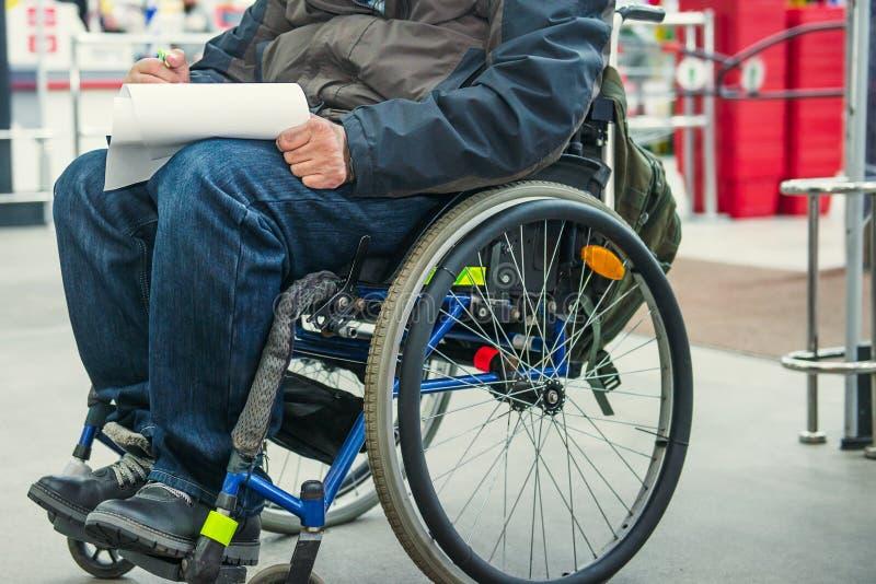 Kein gesperrtes Gesicht, Behinderte auf fahrbarem Stuhl füllt den Formfreien raum oder macht eine Einkaufsliste im Marktplatz vor stockfoto