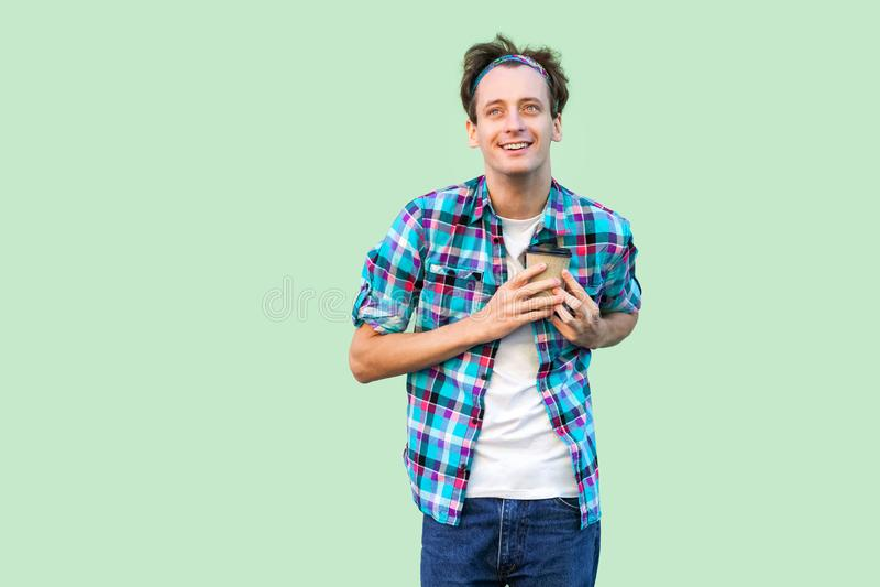 Kein Leben ohne Kaffee Hübscher junger erwachsener Hippie-Mann im weißen T-Shirt und karierten im Hemd, die Papierschale mit Morg lizenzfreie stockbilder