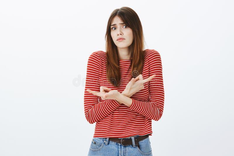 Keine Ideen, wohin man, Hilfsmädchen wählen geht Verwirrte attraktive Frau in den Streifen beschichten, kreuzen Hände und herein  stockfoto
