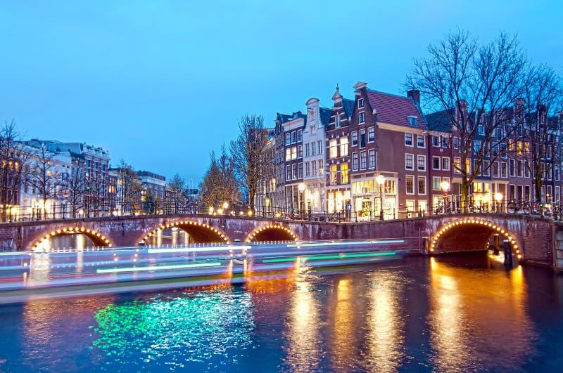 Keizersgracht brosikt av den Amsterdam kanalen och historiska hus under skymningtid, Netherland arkivbild