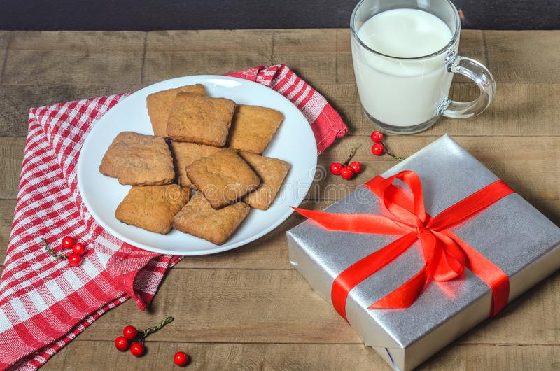 Kekse, Milch und Geschenke auf einer roten Serviette lizenzfreie stockfotos