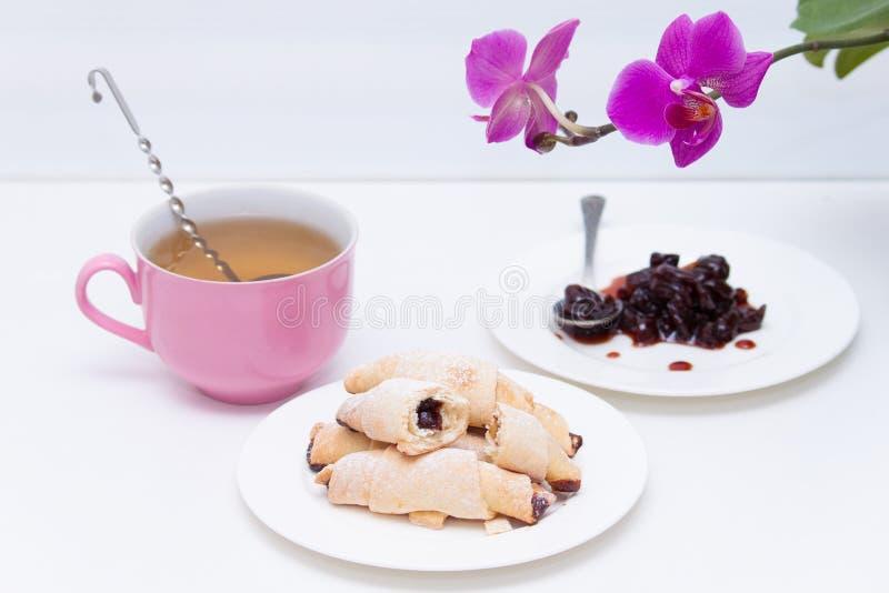 Kekshörnchen mit Stau und Tasse Tee auf weißem Hintergrund lizenzfreie stockfotos