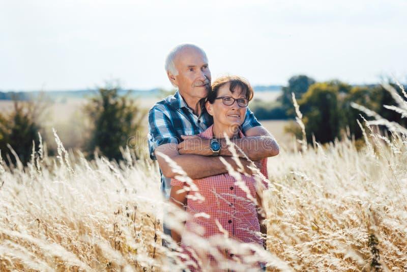 Kel för hög man med hans fru i gräset arkivbilder