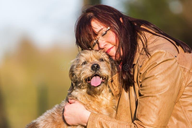 Kel för ung kvinna med en gullig hund arkivbilder
