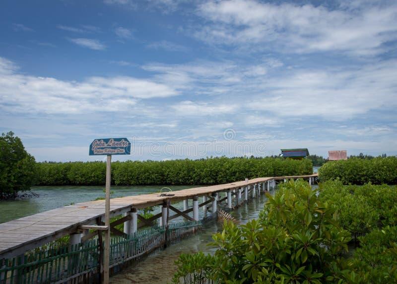 Kelapa ö, Indonesien - December 24, 2017: Joka Landro, träbro som leder till sväva stuga två i mitt av arkivfoton