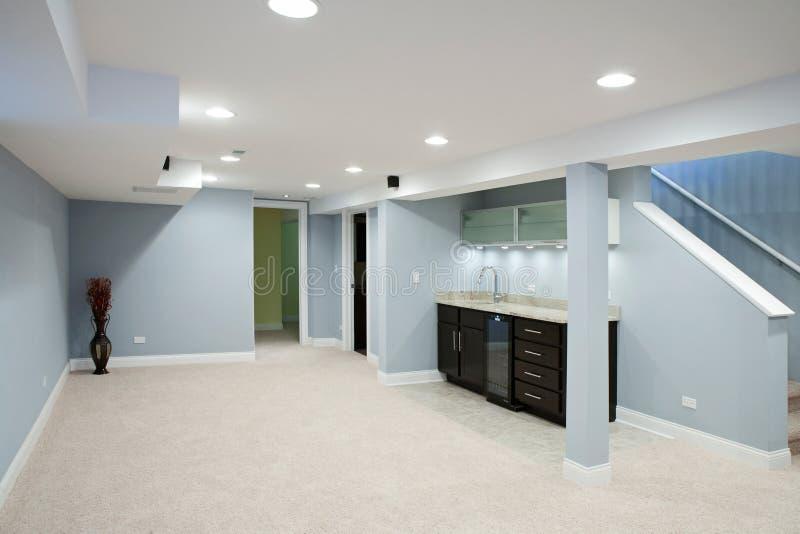 Keller mit Steingegenoberseiten und Teppichboden. stockbild