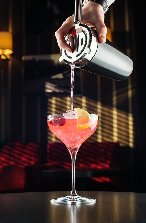Kellner bei der Arbeit, Cocktails vorbereitend Strömender Margarita zum Cocktailglas stockfotografie