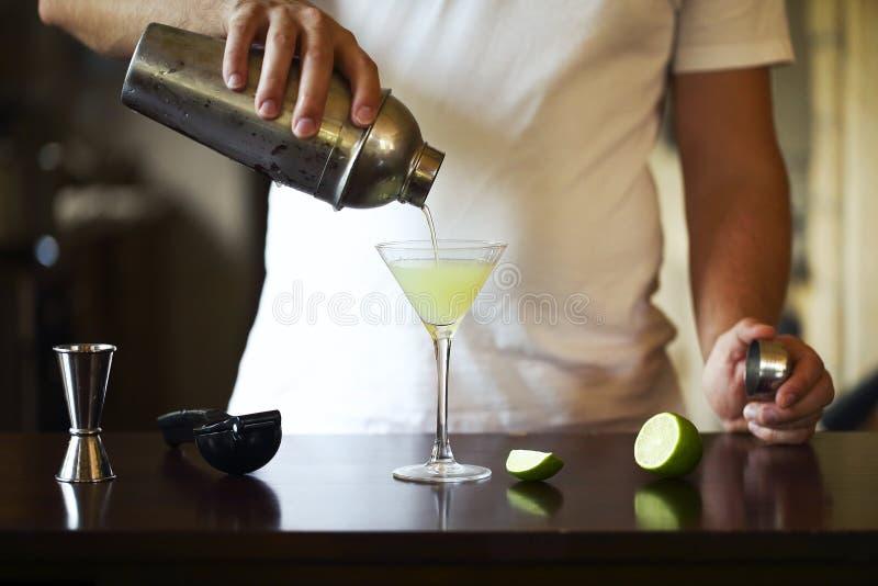 Kellner bei der Arbeit, Cocktails vorbereitend Strömender Martini zum Cocktailglas lizenzfreie stockfotos