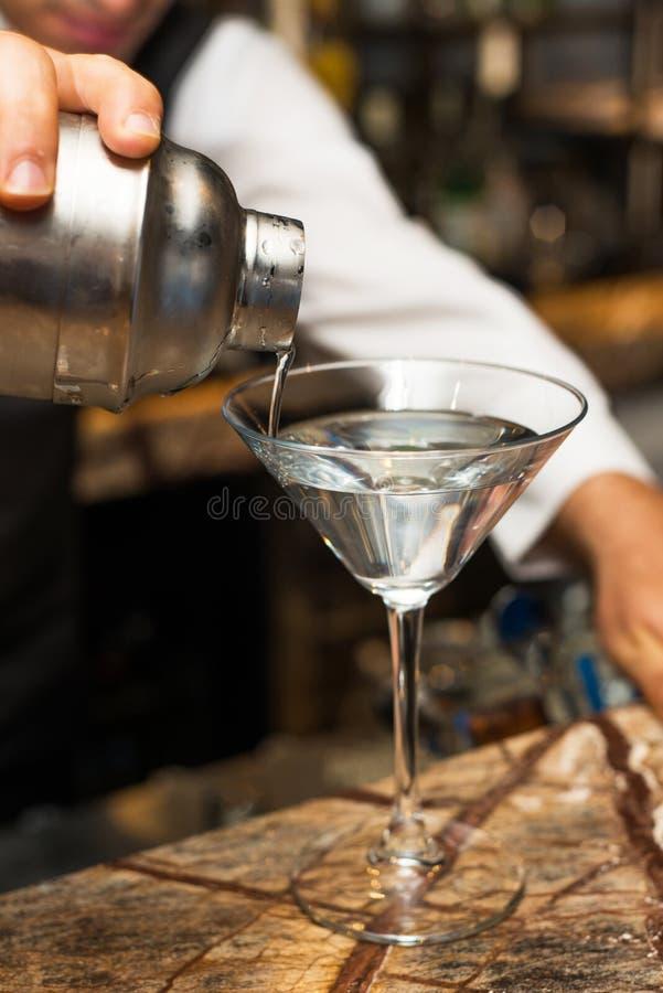 Kellner bei der Arbeit, Cocktails vorbereitend strömendes Cocktail zum Glas stockbild