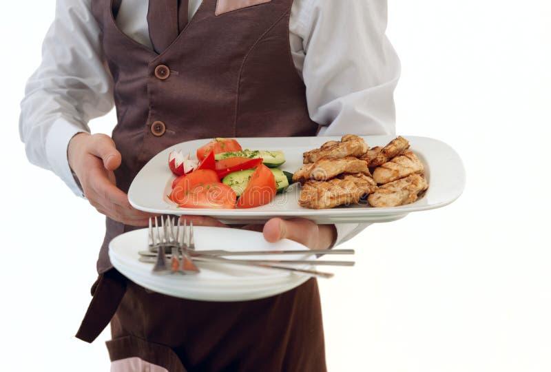 Kellner bietet Fleisch und Gemüse an lizenzfreie stockbilder