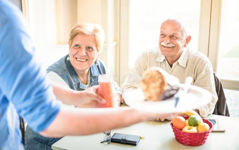 Kellner, der älteren Paare die im Ruhestand essen am Restaurant des strengen Vegetariers dient stockfotografie