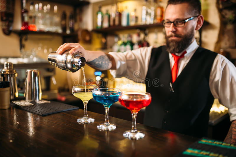 Kellner, der Alkoholcocktails im Nachtklub macht stockbilder