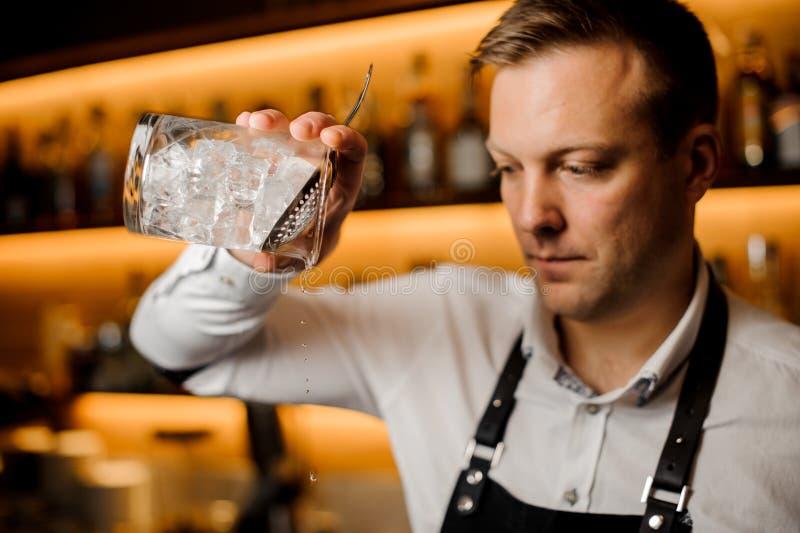 Kellner, der alkoholisches Cocktail mit Eis unter Verwendung des Siebs und des Glases mischt stockbild