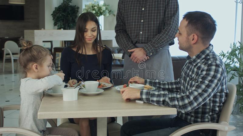 Kellner, der bei Tisch Bestellung der Familie zu Abend isst zusammen entgegennimmt Sie schauend glücklich und erfüllt stockbilder