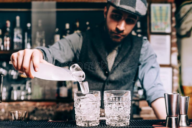 Kellner, der Cocktails, auslaufendes Eis und wiskey in den frischen alkoholischen Getränken vorbereitet lizenzfreie stockfotos