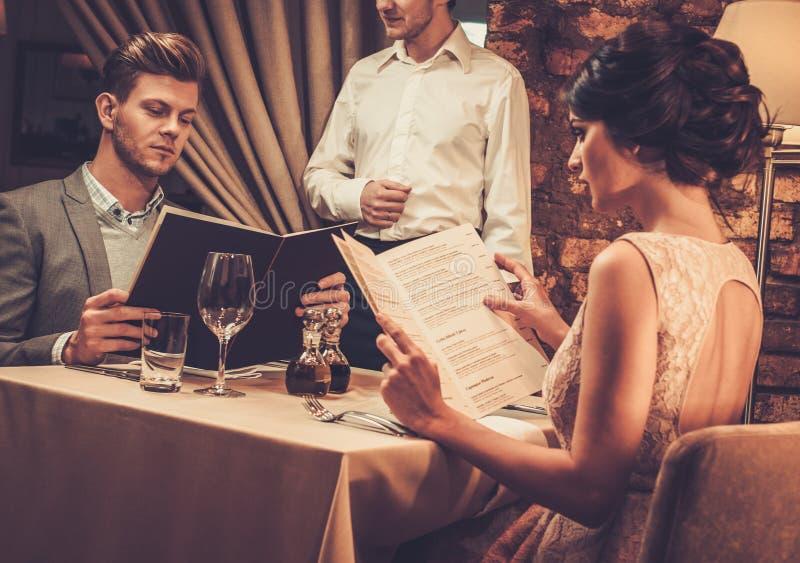 Kellner, der das Menü wohlhabenden Paaren im Restaurant erklärt stockfoto