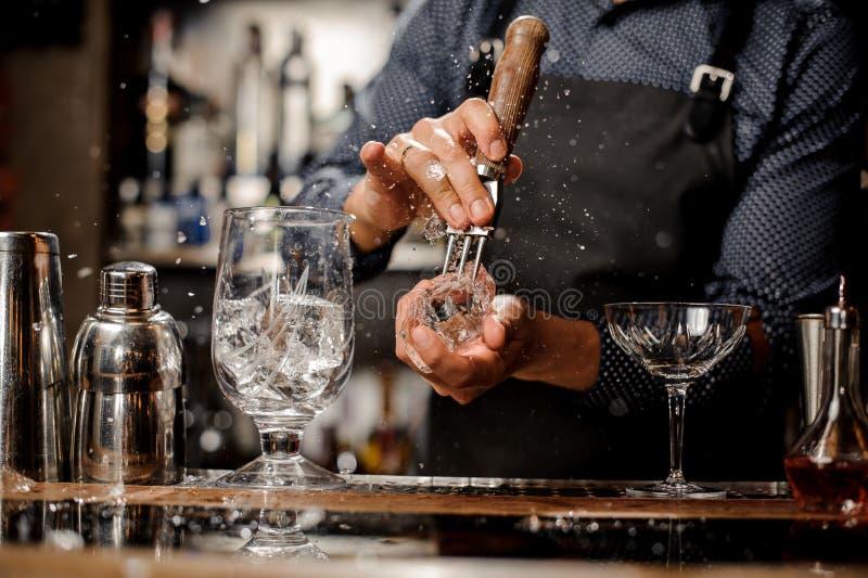 Kellner, der ein großes Stück Eis für ein Cocktail auf dem Barzähler zerquetscht stockbilder