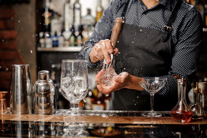 Kellner, der ein großes Stück Eis für ein Cocktail zerquetscht stockfoto