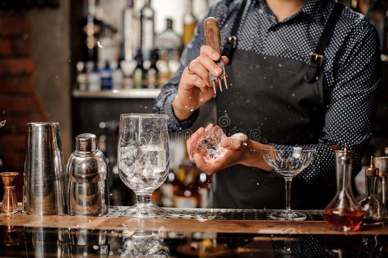 Kellner, der ein großes Stück Eis für die Herstellung eines Cocktails zerquetscht stockbild